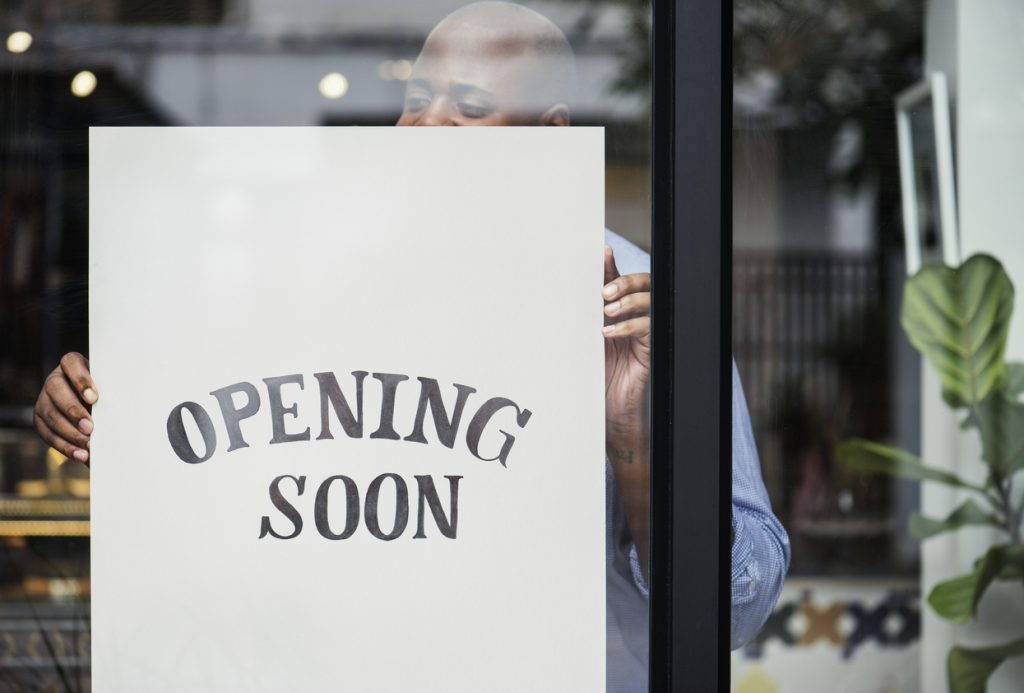 Man putting on store opening soon sign. concept: Planning for Business Reopening