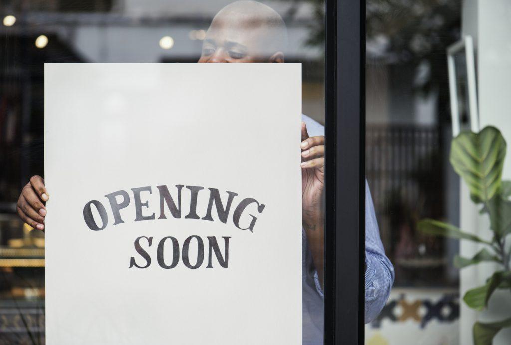 """Hombre poniendo letrero de """"se abre pronto"""" en su negocio. concept: reabriendo tu negocio"""