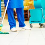 Female cleaner worker in uniform with mop cleaning the floor of supermarket shop store. concept: COVID-19 Best Practices