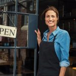 Portrait of a happy waitress standing at restaurant entrance. Portrait of mature business woman in black apron ready to attend new customers in her just opened coffee shop. Happy beautiful woman owner showing open sign in her small business shop. concept: Restaurant reopening plan