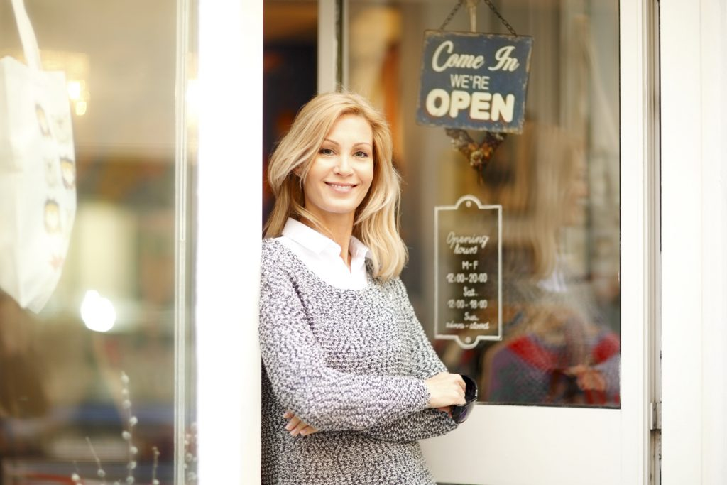 Portrait of attractive clothing store owner standing in her shop entrance. Small shop owner looking at camera and smiling. concept: Reopening Plan