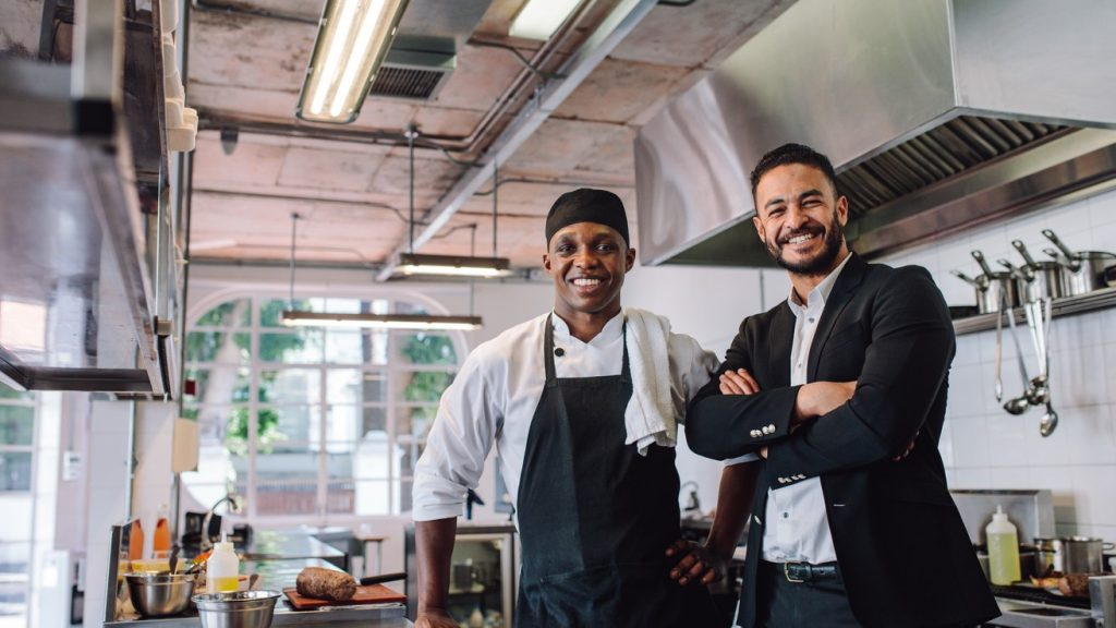 Portrait of restaurant owner with chef in kitchen. Businessman with professional cook standing together and looking at camera. concept: doordash app