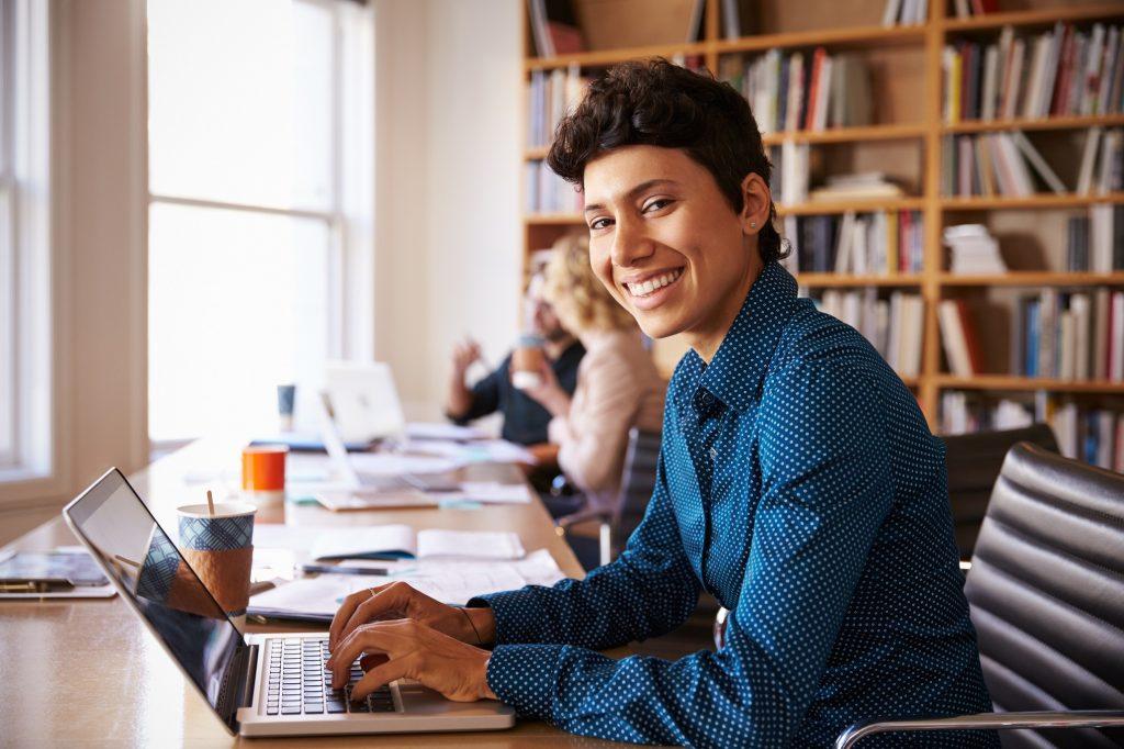 Mujer de negocios usando una computadora en su oficina. concept: Cómo mantenerse positivo durante el coronavirus