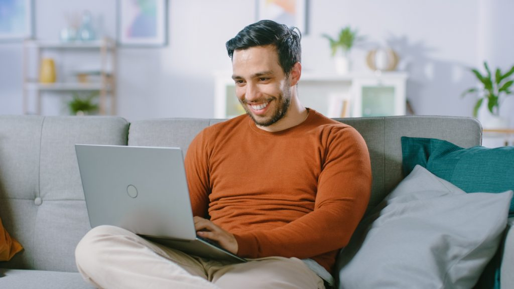 Cheerful Young Man Sitting on a Sofa Holds Laptop on His Lap, Browses Through the Internet, Social Networks, Does e-Shopping. Man at Home Using Laptop while Sitting on a Couch. concept: how to stay positive during coronavirus