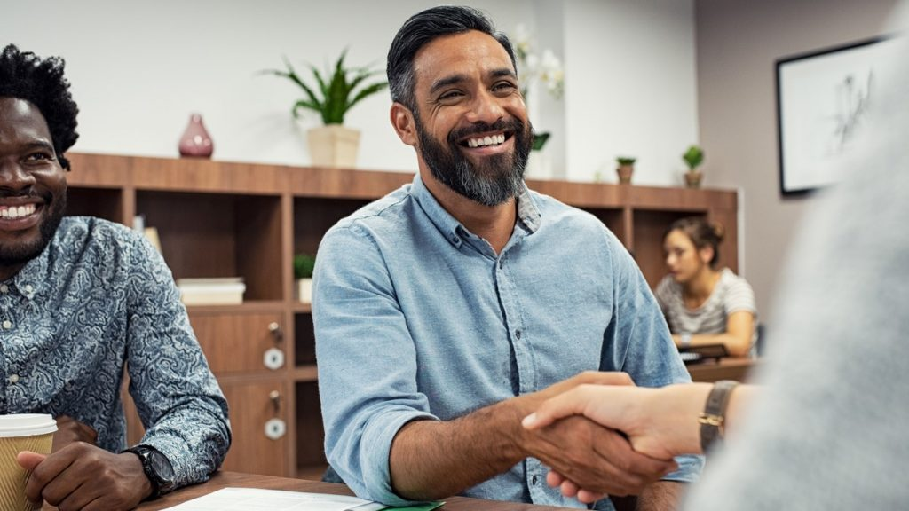 Two business people shaking hands while sitting in meeting room. Middle eastern businessman shake hands to businesswoman. Portrait of happy smiling latin man signing off deal with an handshake. concept: Small Business Grants in Colorado