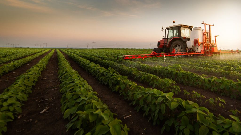 Tractor spraying pesticides on soybean field with sprayer at spring. concept: farm financing