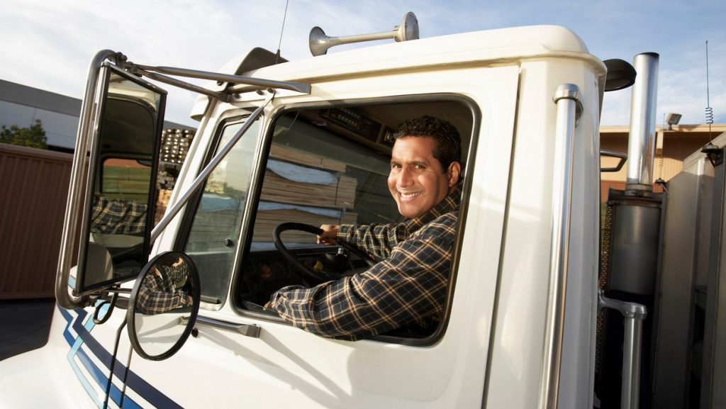 Truck Driver Behind the Wheel. concept: Trucking Business Loans