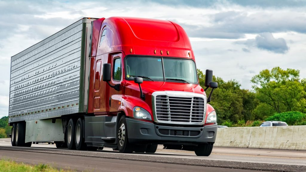 Horizontal shot of a red semi-truck on an interstate highway. concept: Trucking Business Loans