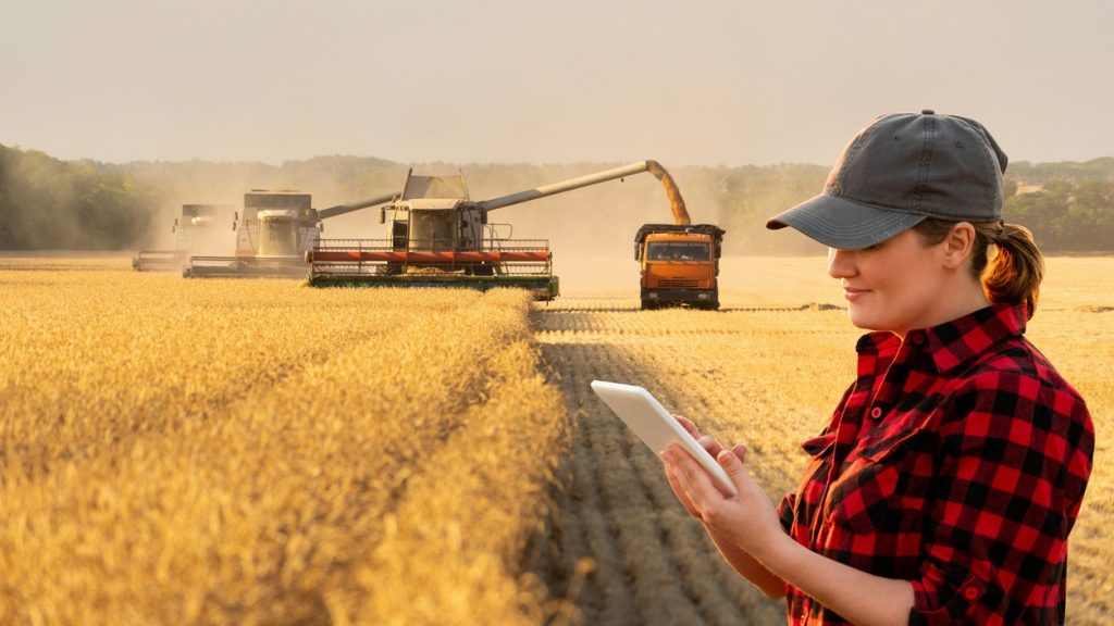 Woman farmer with digital tablet on a background of harvesters. Smart farming. concept: small farm loans