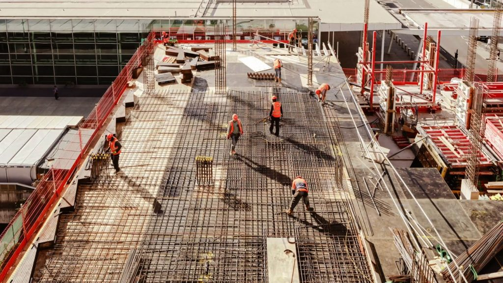 Construction workers at a construction site viewed from above, High angle view of five people with helmets. concept: Construction Loans Rates