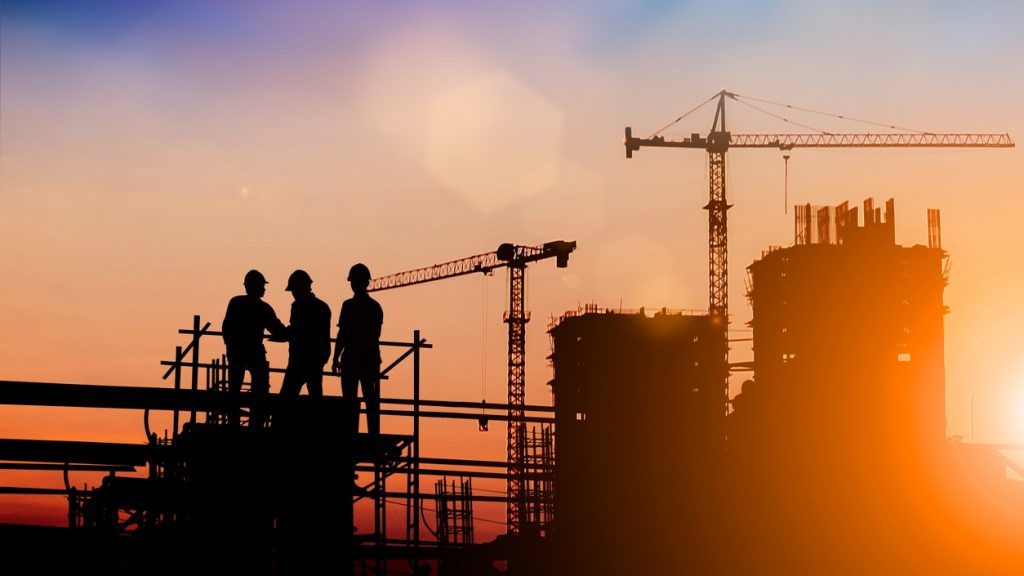 Silhouette of engineer and construction team working at site over blurred background for industry background with Light fair.Create from multiple reference images together. concept: Commercial Construction Loans