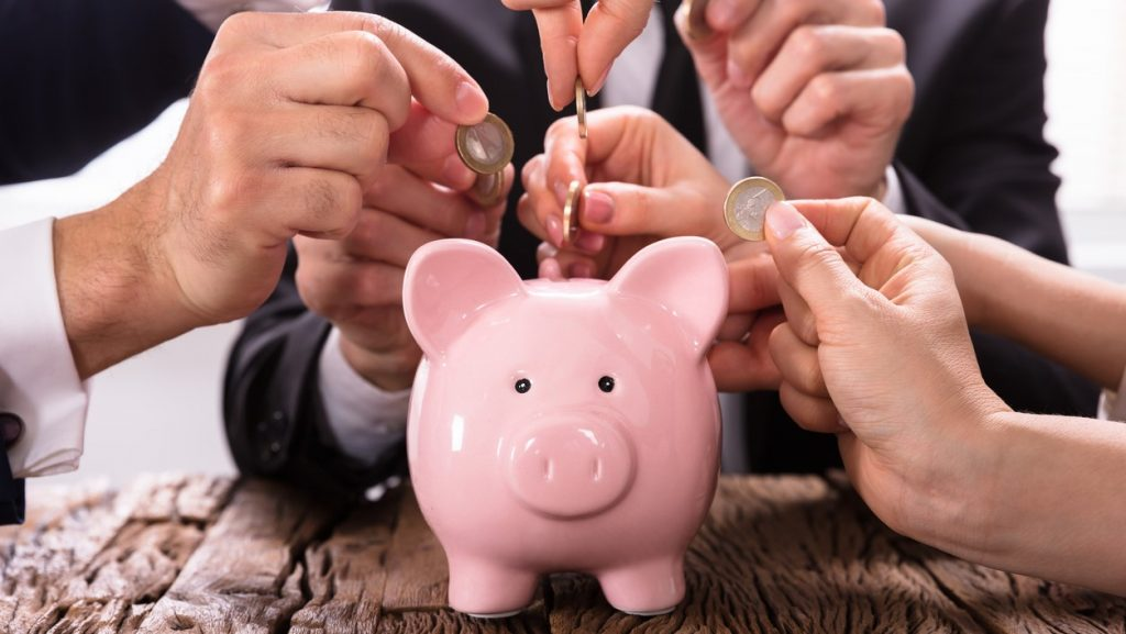 Crowdfunding Concept. People Inserting coins into piggybank. concept:How to Calculate Retained Earnings