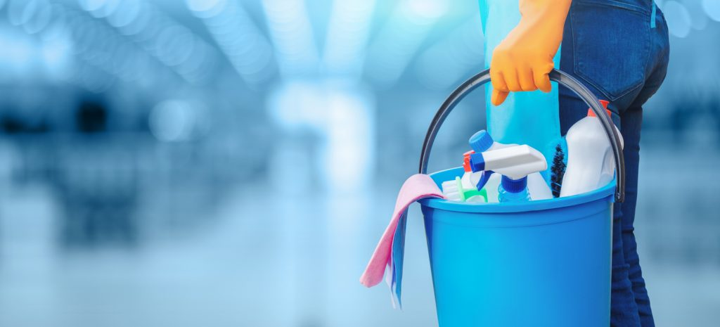 Concept of quality cleaning. The cleaning lady standing with a bucket and cleaning products. concept: Cleaning business