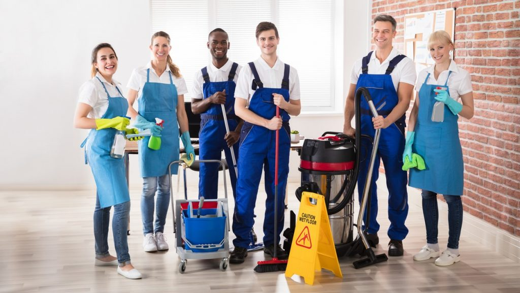 Portrait Of Happy Diverse Janitors In The Office With Cleaning Equipments. concept: cleaning business