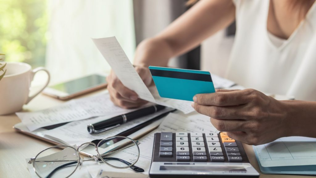 Young woman checking bills, taxes, bank account balance and calculating credit card expenses at home. concept: How Long Does It Take to Build Credit