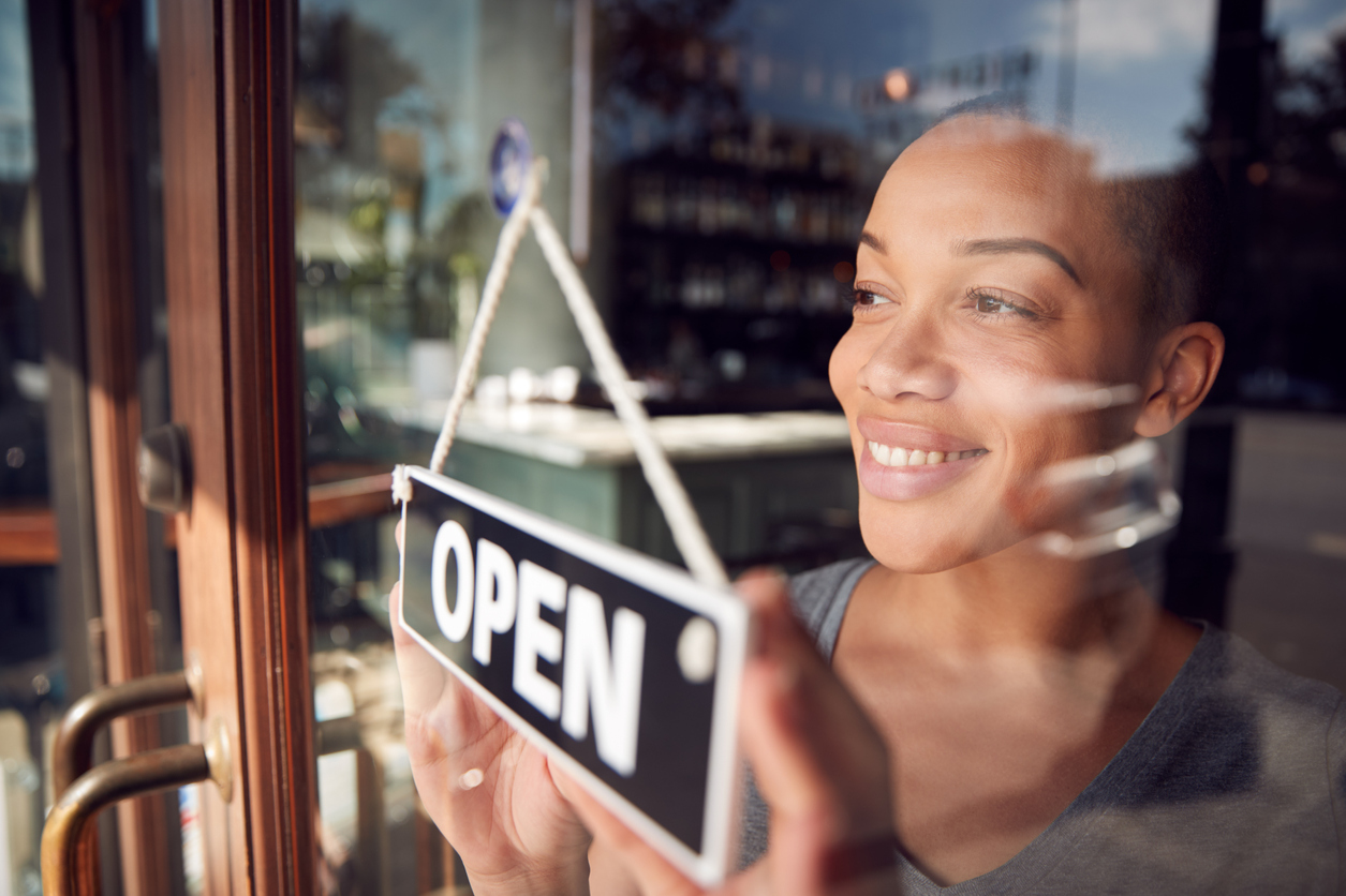 Female Owner Of Start Up Coffee Shop Or Restaurant Turning Round Open Sign On Door. concept: Least Profitable Small Businesses