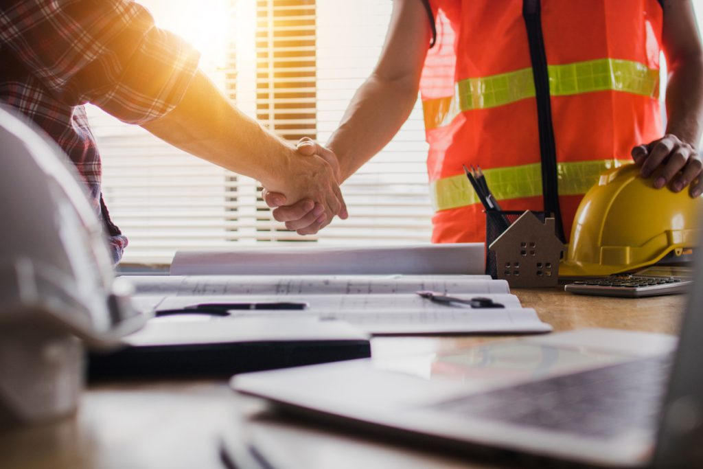 Handshake of two business man, after  architect working and planning blueprint, Engineering objects on workplace. concept: COVID renovations