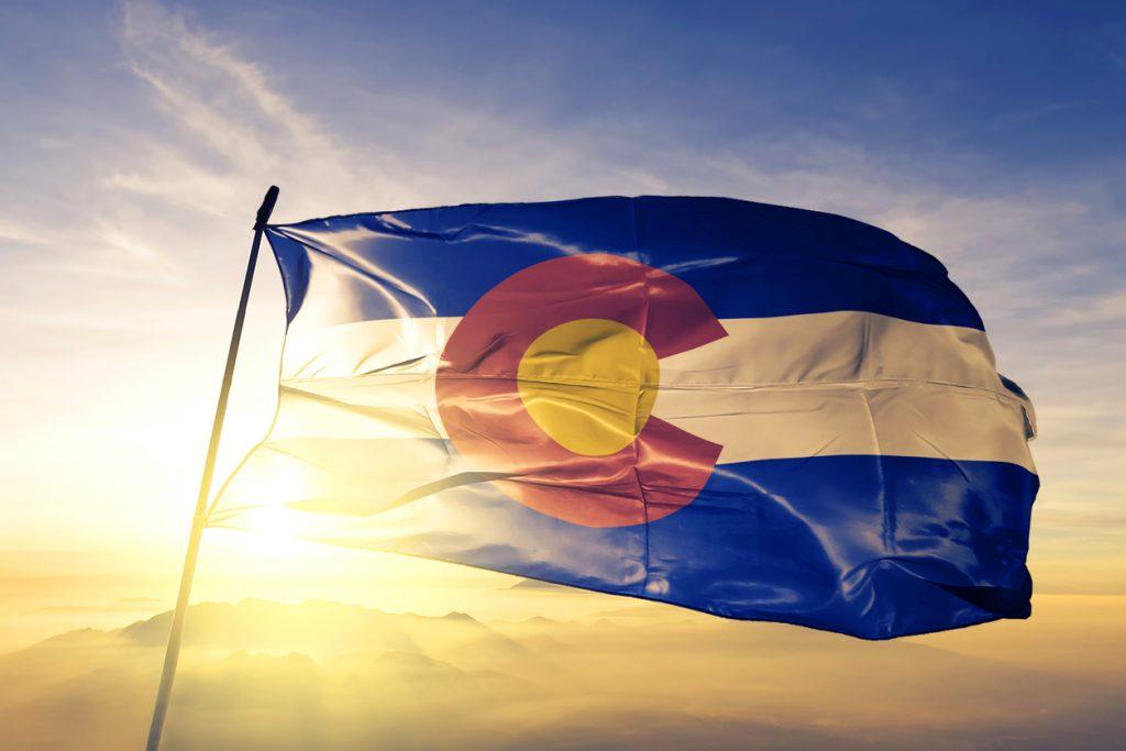 Colorado state of United States flag on flagpole textile cloth fabric waving on the top sunrise mist fog