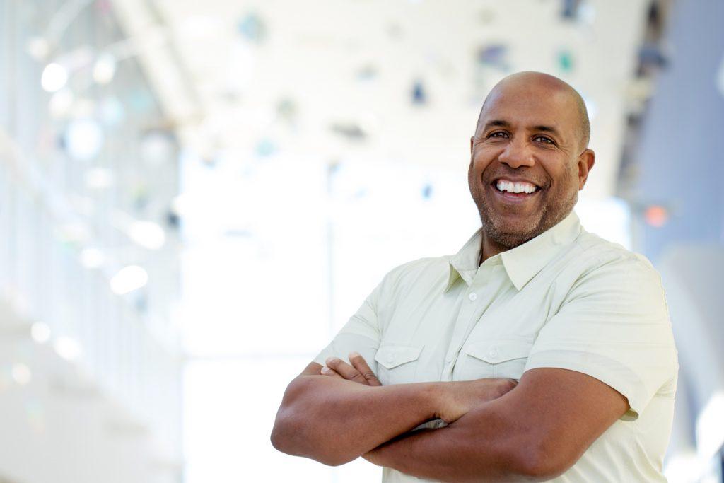 Empresario maduro mirando a la cámara y sonriendo. concept: certificiado de cumplimiento