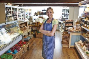 Owner Of Delicatessen Standing In Shop. concept: Mom and Pop Business Funding