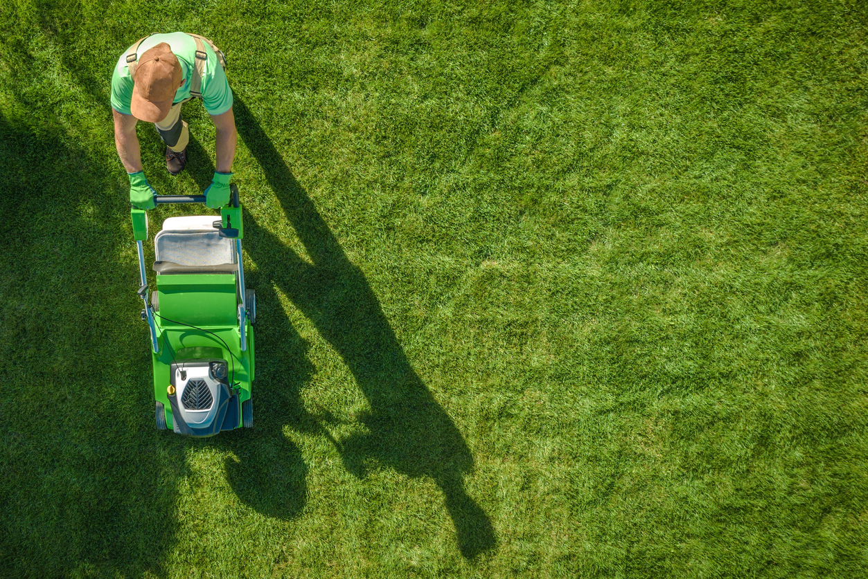 Lawn Moving Aerial Photo. Caucasian Gardener with Gasoline Grass Mower at Work. Landscaping Business. Industrial Theme. concept: Landscaping Business Loans