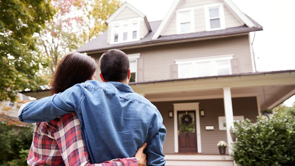 Rear View Of Loving Couple Looking At House. concept: Mortgage Loans for Minorities