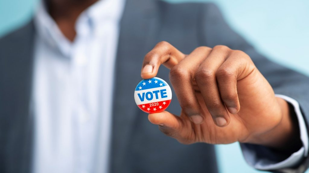 African man holding vote button on blue background for the November elections in the United States 2020, blurred. concept: Small business owner, election day