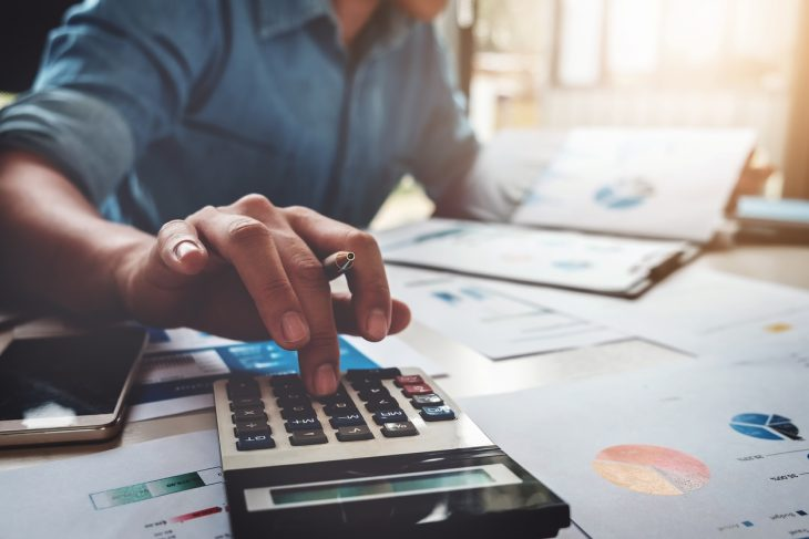 Business accounting concept, Business man using calculator with computer laptop, budget and loan paper in office. concept: Business Line of Credit Calculator