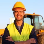Construction driver with excavator on the background. concept: Heavy Equipment Manufacturers