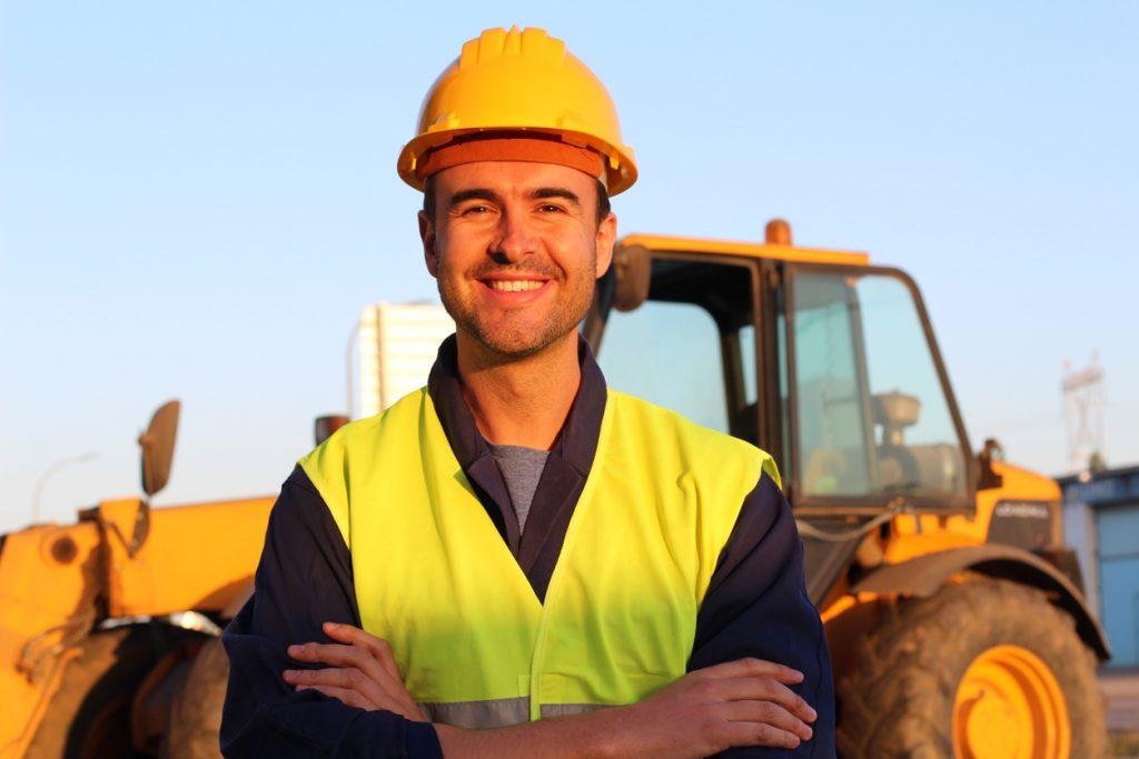 Conductor de construcción con excavadora al fondo. concept: maquinaria de construcción