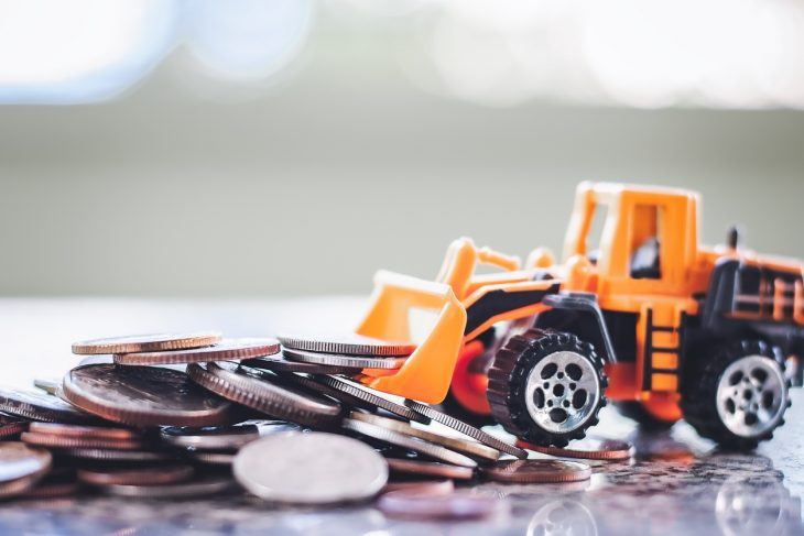 The yellow toy bulldozer with pile of coins against blurred background for saving money, investment, business and finance. concept: Heavy Equipment Financing