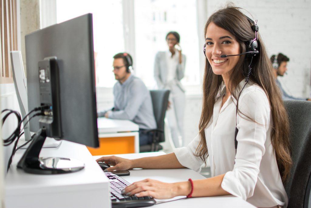Operadora de servicio al cliente amigable con auriculares trabajando en un call center. concept: servicio al cliente online