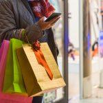 Persona haciendo compras navideñas frente a escaparate sosteniendo bosas con compras. concept: Fiestas decembrinas durante el COVID-19
