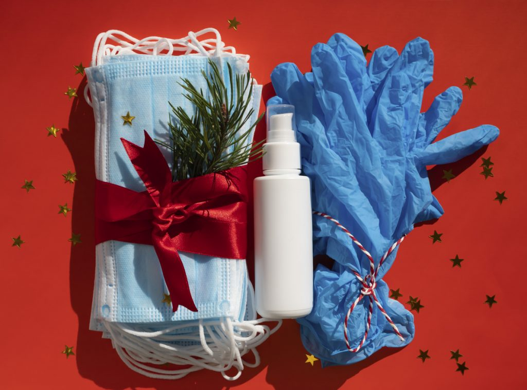 Hygienic face masks antibacterial gel and medical gloves as a gift with a red ribbon, Christmas and New Year 2021 decor on a red background. Holidays self-isolation and coronavirus. concept: Holidays during COVID-19