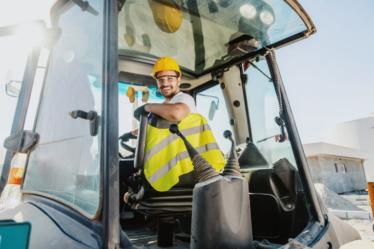 Smiling handsome caucasian worker in overall and with helmet on head driving excavator. concept: small construction equipment