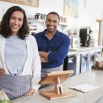Mixed race couple behind the counter at their coffee shop. concept: Black and Brown Communities