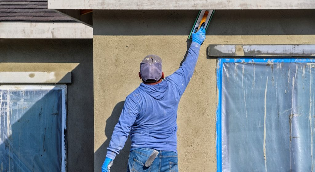 California, USA - October 25, 2019: Renovation at home. construction worker putting decorative plaster on house exterior. concept: construction success story