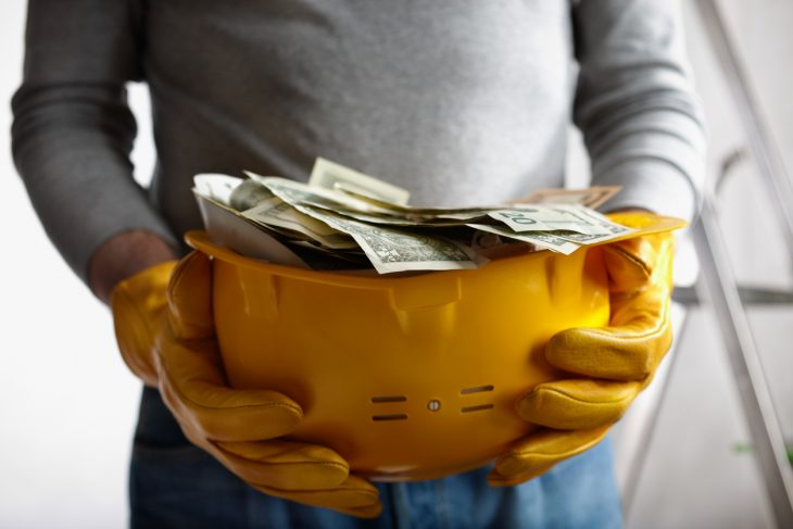 financial concept with dollars and yellow hardhat, selective focus on nearest part. concept: construction factoring