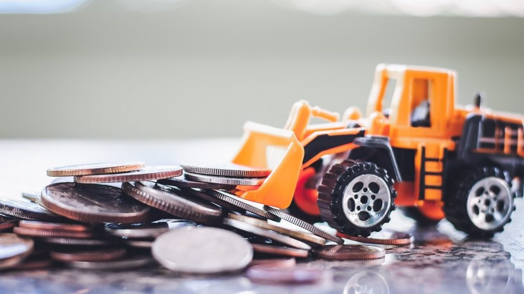 The yellow toy bulldozer with pile of coins against blurred background for saving money, investment, business and finance. concept: construction factoring