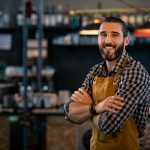 Happy satisfied bartender wearing apron while standing near counter with crossed arms and looking at camera. Confident coffee shop waiter smiling at cafeteria. Successful proud young brewer at his pub with copy space. concept: business mistakes