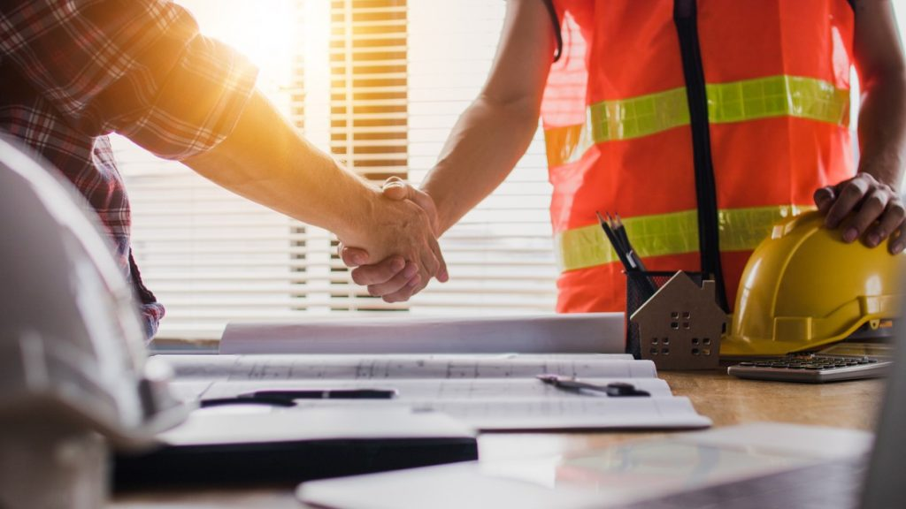 Handshake of two business man, after architect working and planning blueprint, Engineering objects on workplace. concept: Construction Quote Template