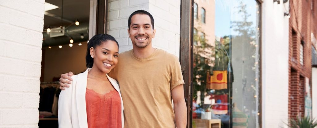 Young Hispanic couple smiling to camera outside their shop. concept: Small Business Plan