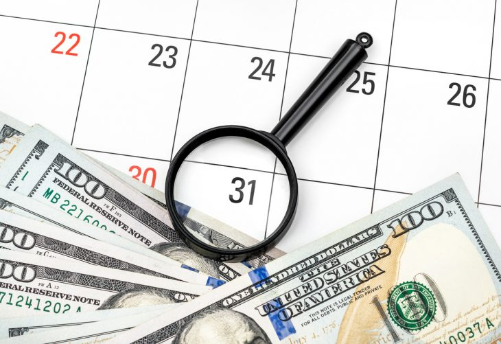 Magnifying glass with money on calendar. Focus on last day of month. Business. concept: Monthly payments
