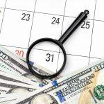 Lupa con dinero en calendario. Concept: pagos mensuales