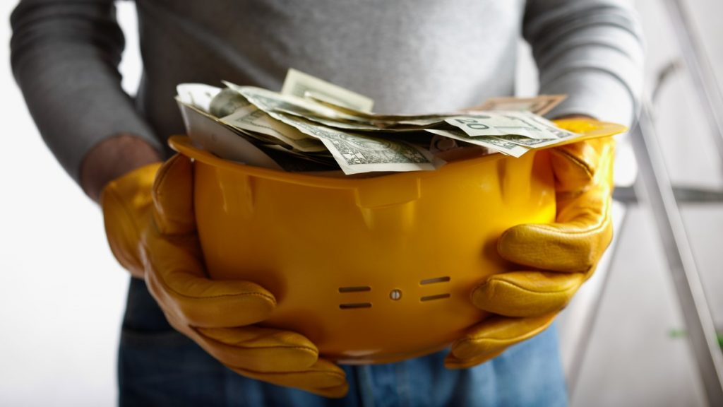 financial concept with dollars and yellow hardhat, selective focus on nearest part. concept: construction calculator