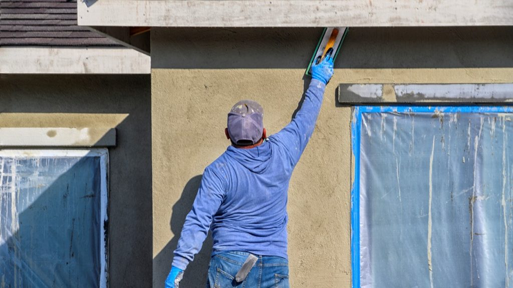 California, USA - October 25, 2019: Renovation at home. construction worker putting decorative plaster on house exterior. concept: construction calculator