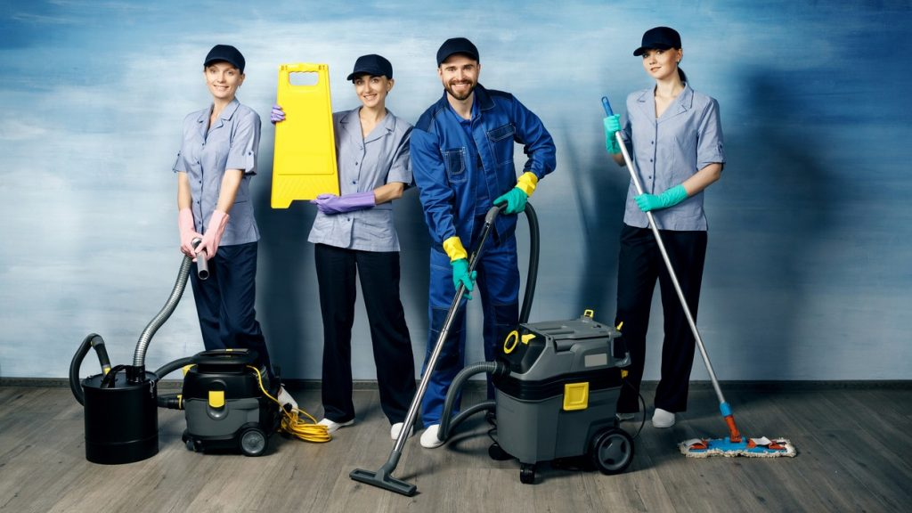 Three attractive girls and one young man with a beard in a working uniform for cleaning are holding items for cleaning on a blue background. concept: Commercial Cleaning Business