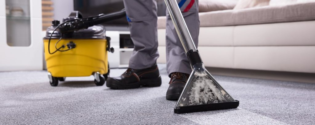 Low Section Of A Person Cleaning The Carpet With Vacuum Cleaner In Living Room. concept: Commercial Cleaning Business