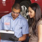 Mechanic in auto repair shop works with customer. concept: Auto Repair Invoice