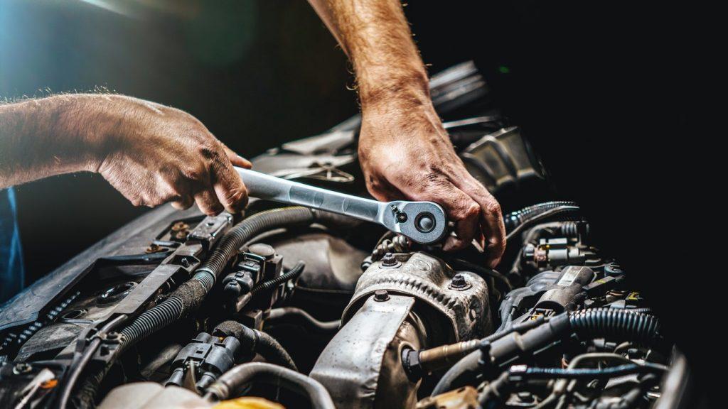 Taller de reparación automotriz, mecánico trabajando en el motor de un coche. concept: programa de reparación directa